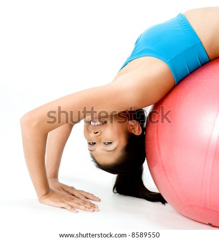 A slim young woman stretching over a fitball