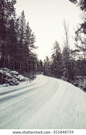 A slippery and curvy road in the winter. Image taken in Finland during sunrise on a cold morning. First snow is covering up the road and forest. Image has a vintage effect applied.