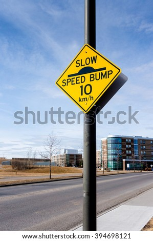 A slow down traffic sign in a residential area indicating a speed bump and a 10 km per hour driving speed. - stock photo