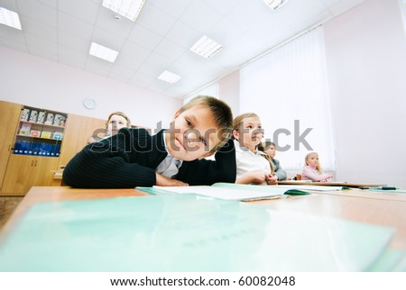 A smal curious boy sits at the desk - stock photo