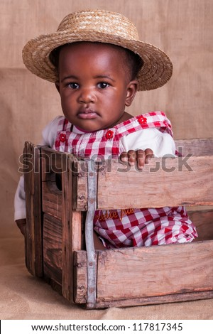 A small African baby girl from the farm in the studio. - stock photo
