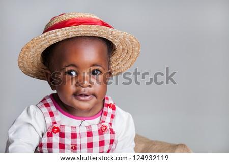 A small African girl dressed as a farm girl in a cradle. - stock photo