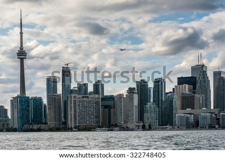 A small airplane flies above the skyscrapers and television tower of Old Toronto. View from Algonquin island, Canada - stock photo