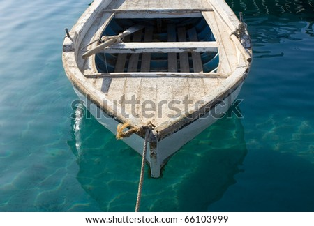 A small anchored fishing boat near the beach. The Photo was shot at Hurghada, Egypt, early in the morning. - stock photo