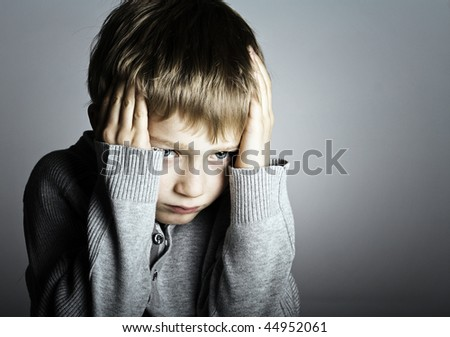 a small and frightened blonde boy covers his head and ears for protection