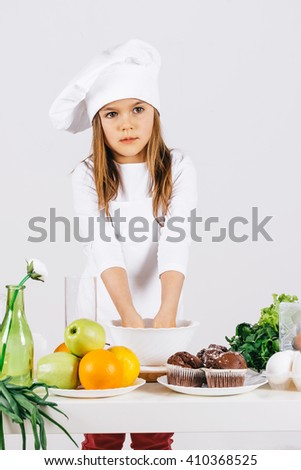 A small and funny little girl in a cap cook with fresh food in the kitchen on a white background - stock photo