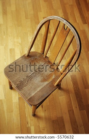 A small antique wooden chair sits on an oak hardwood floor.