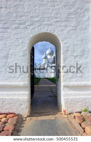 a small arched door in the large white stone wall and church behind it
