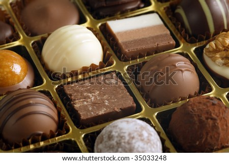 A small assortment of chocolate truffles and pralines in a box.  Very Shallow depth of field, focusing across the middle. - stock photo