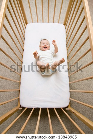 A small baby girl lying in a crib - stock photo