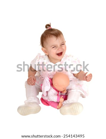 A small baby girl sitting on the floor, laughing and playing with her