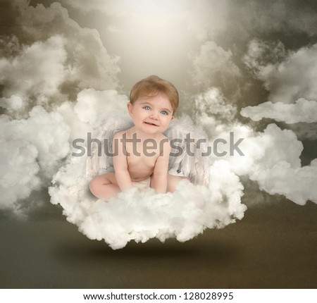 A small baby is sitting on top of a cloud as an angel with wings and looks happy for a faith or beauty concept. - stock photo