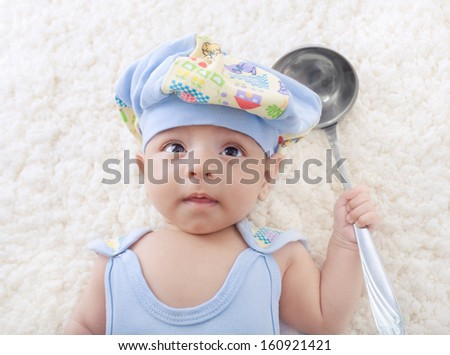 A small baby lying with a scoop - stock photo