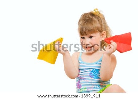 a small baby plaing with red and yellow paper airplane made hands