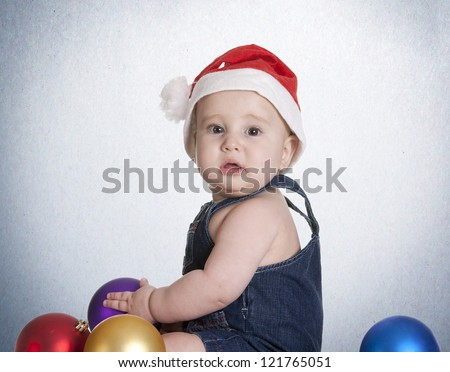 a small baby, playing with the Christmas decorations - stock photo