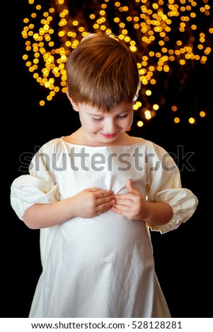 A small backlit boy in front of a starry background looks down and holds the outside of his chest like he is inspecting his heart. He is wearing an old fashioned night shirt.