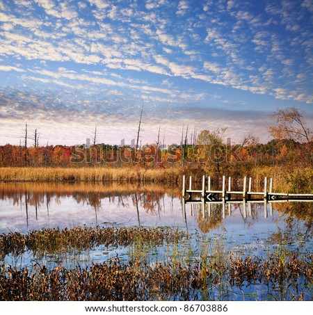 A Small Boat And Fishing Pier Under Beautiful Morning Skies On Lake Sixteen During Autumn, Oakland County Michigan. USA - stock photo