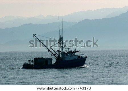 A small boat heads into the foggy Katchemak Bay. - stock photo