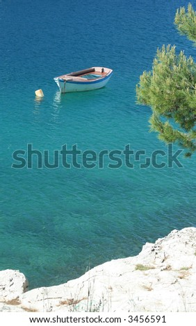 a small boat in a bay at the Croatian coast - stock photo