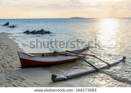 A small boat on a sandy shore