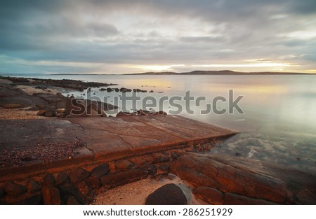 A small boat ramp enters the water on a rocky coastline. - stock photo
