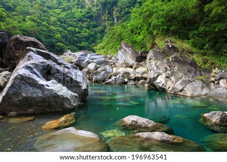 A small body of water surrounded by large rocks and green trees. - stock photo