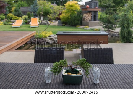 A small bonsai sits on a contemporary backyard patio table between two sculptured candles in sharp focus with a beautifully landscaped yard softly out of focus in the background.   - stock photo