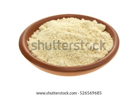 A small bowl filled with ground soy powder isolated on a white background.
