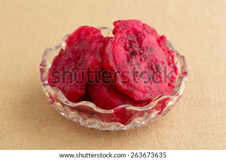 A small bowl filled with slices of prickly pear cactus on a tan table cloth. - stock photo