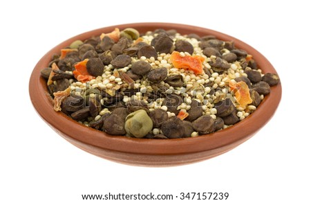 A small bowl filled with the dry ingredients for quinoa lentil soup isolated on a white background. - stock photo