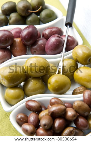 A small bowl of olives on a table  on wooden table - stock photo