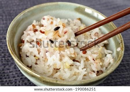 A small bowl of rice sitting upon a burlap mat. - stock photo