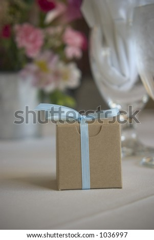 A small box with a ribbon sits on a table with flowers and a beautiful table setting behind it probably a wedding or a fancy celebration - stock photo