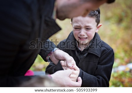 A Small boy crying in pain injuring his hand. Father provides first aid