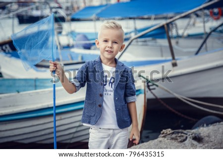 A small boy in a marine style against the backdrop of boats and yachts. Idea and concept Friendship, vacation, vacation, family