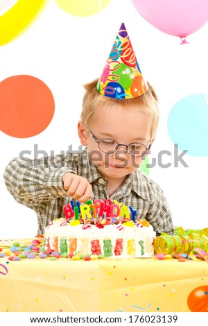 A small boy in a plaid shirt reaching towards a candy covered birthday cake.