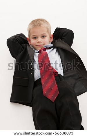 A small boy in the studio, dressed up in a suit and pretending to be a businessman, having a rest. White background.