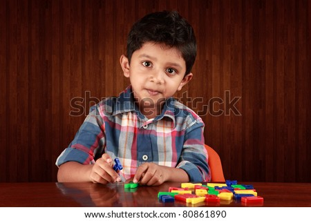 A small boy playing with alphabets - stock photo