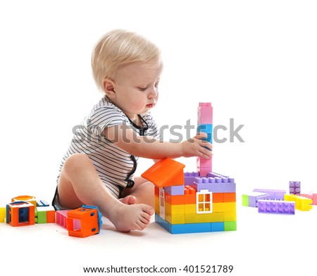A small boy plays by the constructor. Isolated on a white background. - stock photo