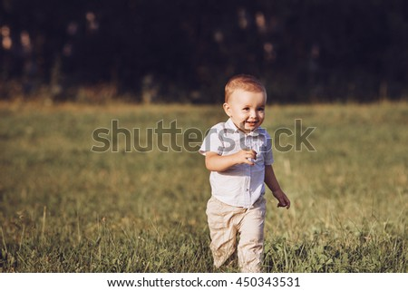 A small boy runs across the field laughing happily - stock photo