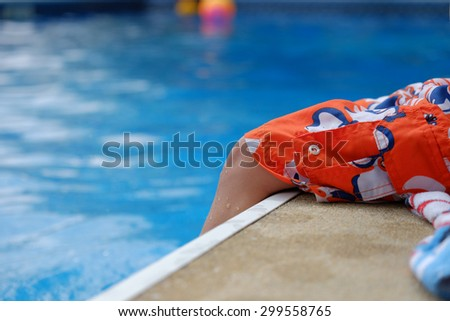 A small boy sits at the edge of a pool with orange swim trunks and dangles his legs into the water - stock photo