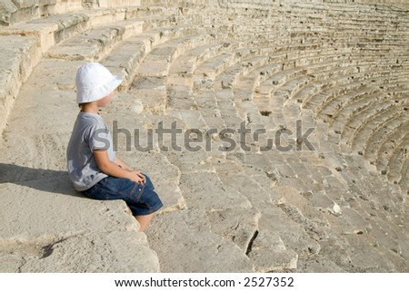 A small boy sitting in an amphitheater - stock photo