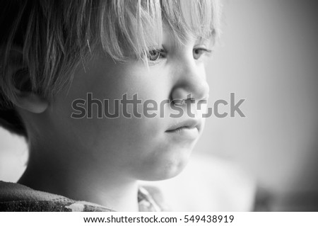 A small boy with a frightened expression on his face depicting the emotion of fear