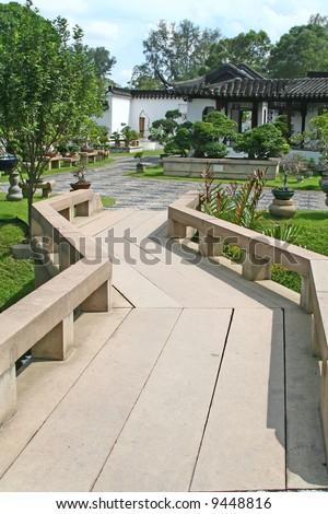 A small bridge leading into a bonsai garden - stock photo