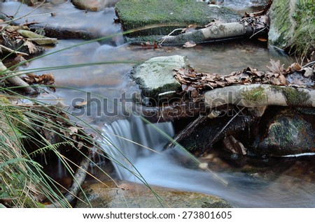 A small brook is running over pebbles in the mountain slope. It is photographed at long shutter speed. - stock photo