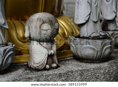 A small Buddha in Japanese shrine. It is made of stone and with a big round head. - stock photo