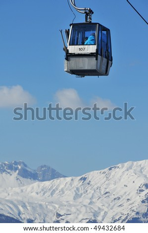 a small cable car for skiers with snow covered mountains in the background - stock photo