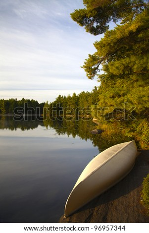 A small canoe stored on a rock by a glassy calm lake in vertical format.