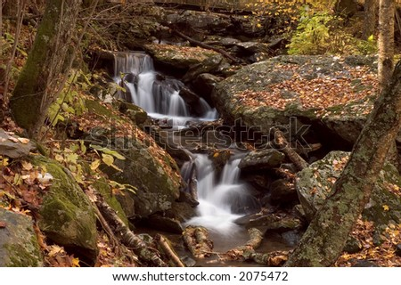A small  cascade in the autumn forests of Virginia. Taken with a slow shutter speed to smooth and soften the water. The stream is framed with large boulders covered with the   leaves of autumn. - stock photo