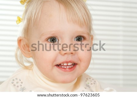A small charming Caucasian girl on light background